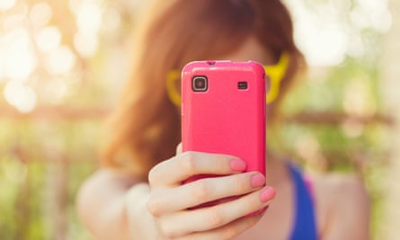 Girl taking a photo with her pink smart phone