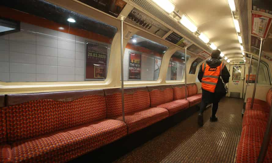 A member of staff in a hi-vis vest walks through an empty train
