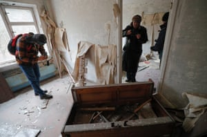 Tourists look round an abandoned flat in the city of Pripyat