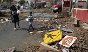 A woman with her two children walk past debris left by Hurricane Irma in Charlotte Amalie, St Thomas, US Virgin Islands