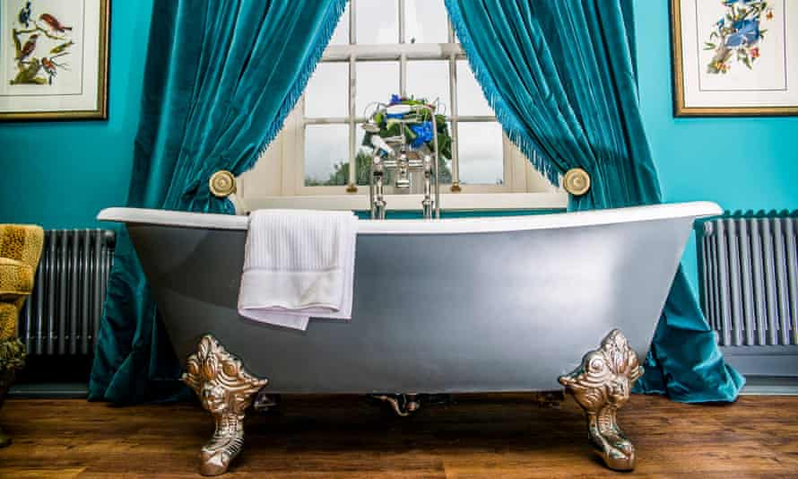 Clawfoot bathtub in a bedroom in front of a window and blue drapes at the Coach and Horses in Bolton-by-Bowland, Lancashire.