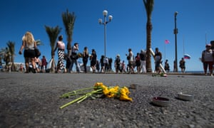 Yellow flowers net to blood stains on the Promenade des Anglais in Nice