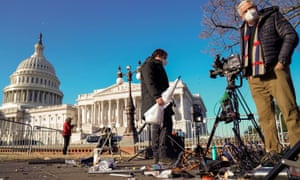 Members of the news media survey damaged equipment outside the US Capitol a day after a mob of Trump supporters breached the building.