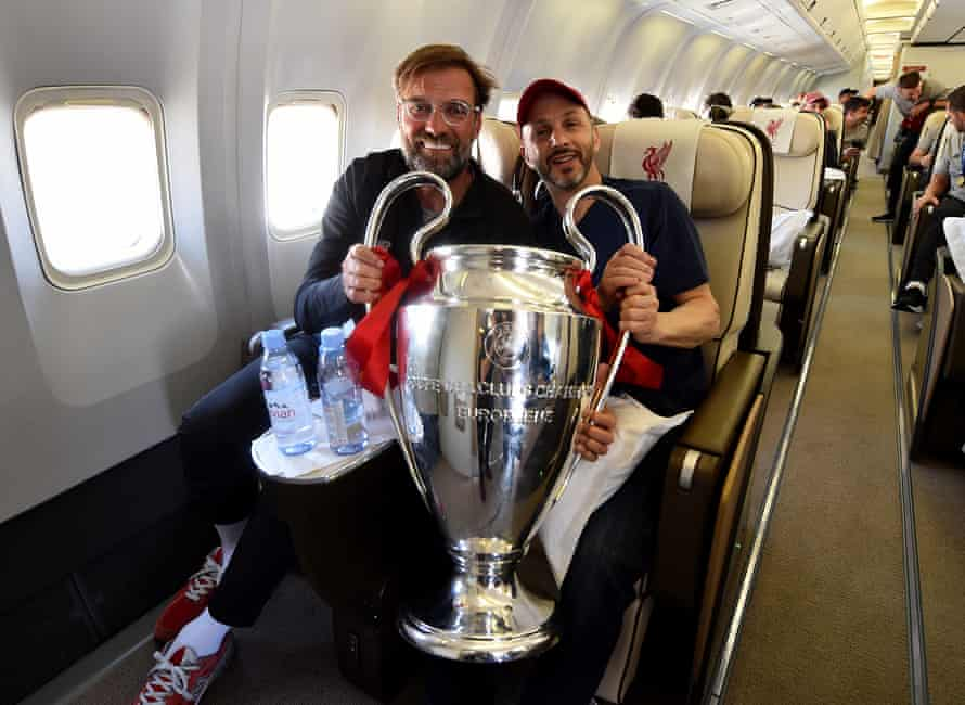 Jürgen Klopp holds the Champions League trophy with Mike Gordon, the FSG president, on the plane back from the 2019 final win in Madrid