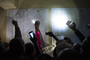 People check names on a voter registration list at the Olympic Primary School in Kibera, one of the largest slums in Africa