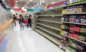 Customers in Puerto Rico walk near empty shelves that are normally filled with bottles of water. The governor has declared a price freeze on basic necessities.