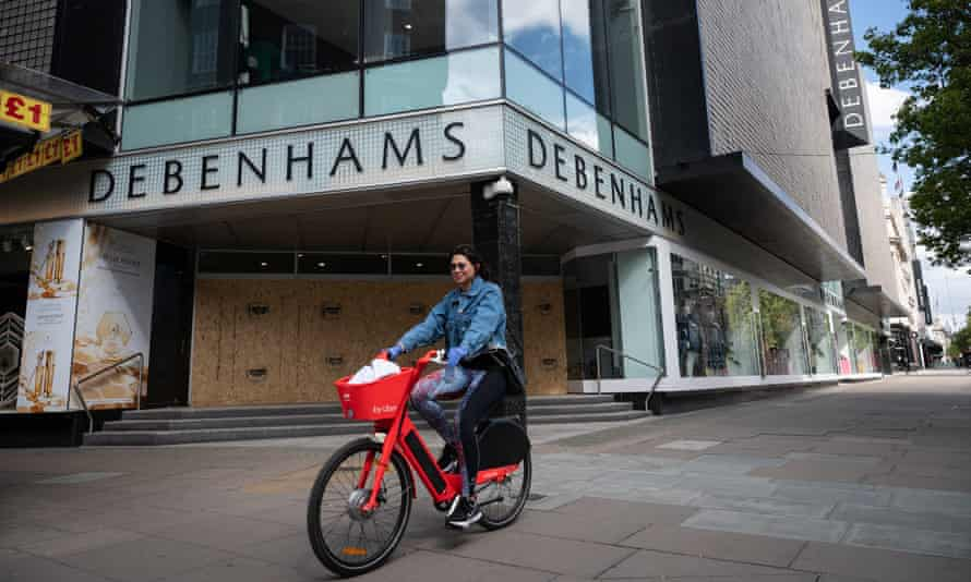 A person cycles past the boarded-up Oxford Street branch of Debenhams in central London