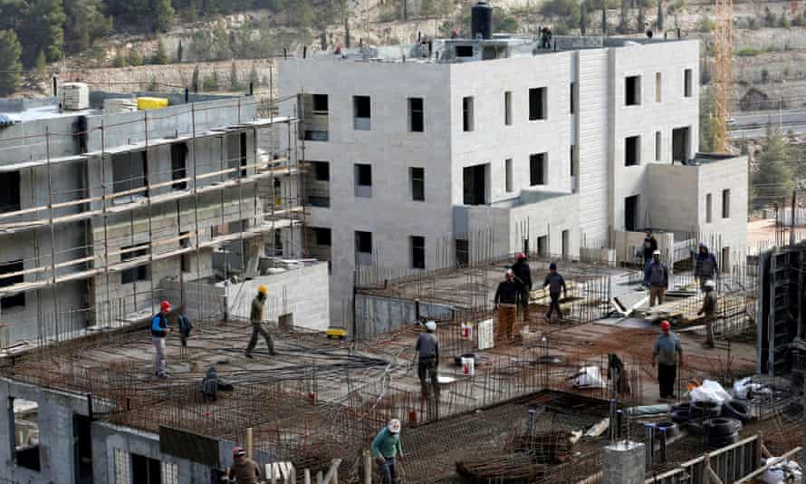 Labourers work at a construction site in the Israeli settlement of Ramot in an area annexed to Jerusalem.