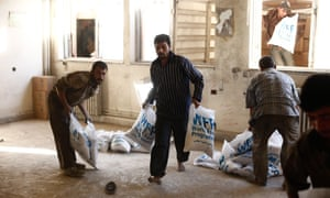 Aid workers sort bags of food in Syria