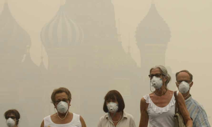 Tourists wear protective face masks as they walk along the Red Square in thick smog resulting from wildfires, August 2010.