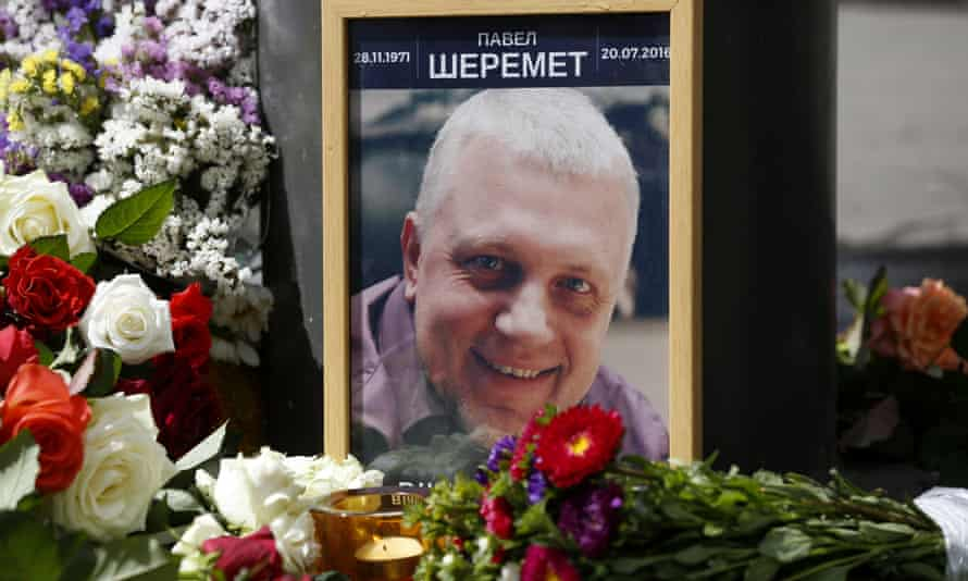 A portrait of Pavel Sheremet surrounded with flowers and candles at the scene of his killing in Kyiv