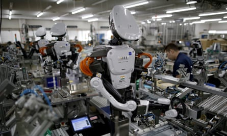 Humanoid robots work side by side with employees in the assembly line at a factory in Kazo, north of Tokyo, Japan.