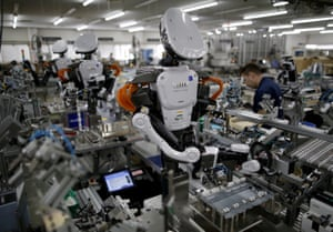 Humanoid robots work side by side with employees in the assembly line at a factory of Glory Ltd., a manufacturer of automatic change dispensers, in Kazo, north of Tokyo.