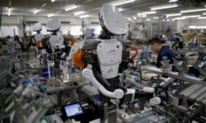 FILE PHOTO: Humanoid robots work side by side with employees in the assembly line at a factory of Glory Ltd., a manufacturer of automatic change dispensers, in Kazo, north of Tokyo, Japan, July 1, 2015. REUTERS/Issei Kato/File Photo