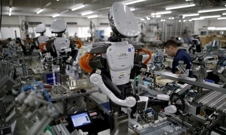 Humanoid robots work side-by-side with employees on an assembly line in Kazo, Japan.