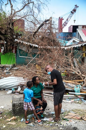 A father hands masks to his family. The burning of heaps of debris and rotten planks of wood has filled the air with abrasive smoke.