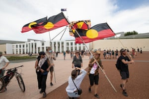 Invasion Day protesters waving the Aboriginal flag on the forecourt of Parliament House in Canberra.