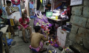Robert Sicat paints a dragon head, but members of his Dragon and Lion dance group must seek other ways to earn a living this year in Manila's Chinatown.