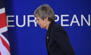 Theresa May walks off stage with union jack and Europe sign in the background