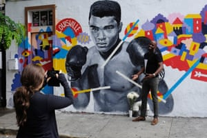 A man has his photograph taken near a makeshift memorial to the late Muhammad Ali in New York