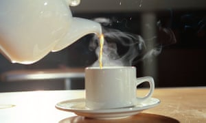 Pouring a cup of tea from a pot.