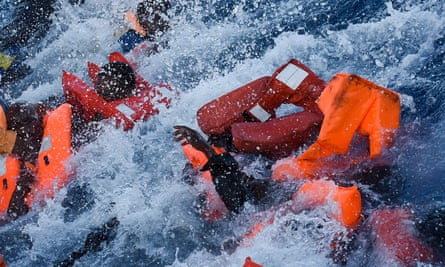 People panic as they fall in the water during a rescue operation off the Libyan coast on Thursday.