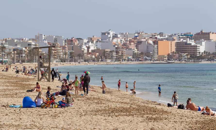 Tourists sunbathe on Palma Beach in Palma de Mallorca in March.