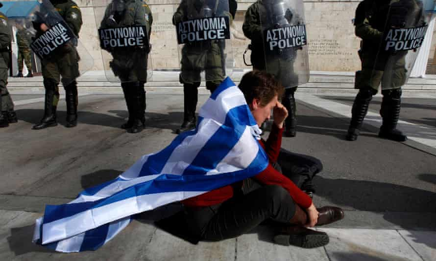 An anti-austerity protester draped in the Greek flag.