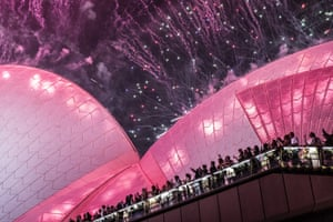 Pink fireworks cover the sky with people watching from the Sydney Opera House