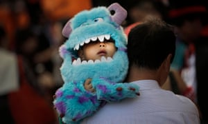 A child in a disguise depicting Sulley from movie Monsters, Inc. participates in a Halloween costume festival in Tokyo