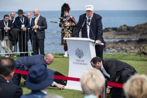 Aides clear swastika golfballs from the grass as Donald Trump speaks.