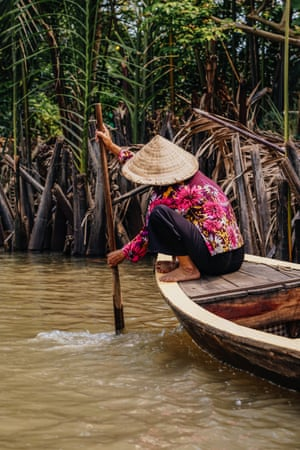 A sampan boat on the Mekong delta in Vietnam, near Ho Chi Minh City. The boatman is trying to free his vessel which is stuck on sandbanks.