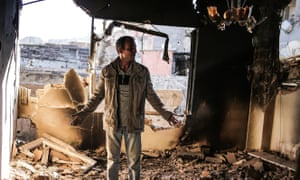 A man looks in shock at his destroyed house in Cizre.