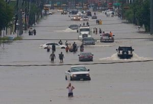 People walk through the flooded waters of Telephone Road