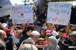 Pope Francis is welcomed by migrants and refugees, holding banners appealing for help, at the Moria refugee camp