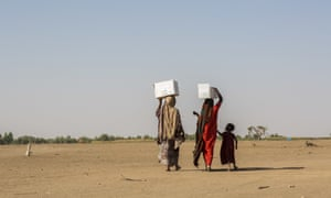 Pastoralist women displaced by drought carry food rations from a distribution point to the Farburo site for internally-displaced people in Gode, in the Somali region of Ethiopia.