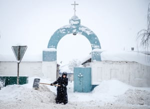A nun removes snow in front of the gate of the convent in the village of Bogoslovo.