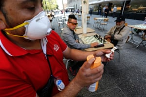 A worker disinfects public chess boards in Santiago city centre to avoid spread of coronavirus on Tuesday