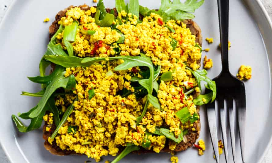 Tofu scramble toast with greens on rye bread, top view.