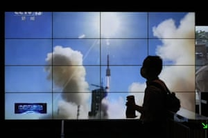A man is silhouetted as she walks by a TV screen showing CCTV live telecast of the Long March-2F Y12 rocket carrying a crew of astronauts in a Shenzhou-12 spaceship lifts off at the Jiuquan satellite launch centre, at a shopping mall in Beijing