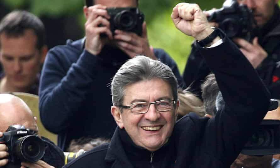 The far-left candidate Jean-Luc Mélenchon waves at supporters as he cruises on a barge on a canal in Paris.