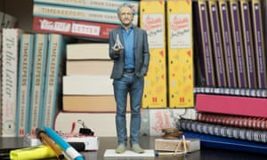 A miniature model of Simon Garfield standing on a desk holding a miniature of the Eiffel Tower, normal size books behind him