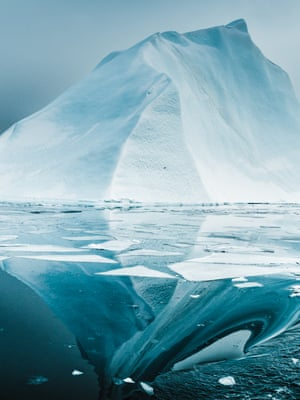 Icefjord Reflections (2018) An iceberg mirrored in calm waters warped in the wake of a passing boat, Ilulissat Icefjord, Greenland