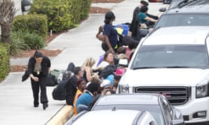 People take cover behind vehicles in Fort Lauderdale.
