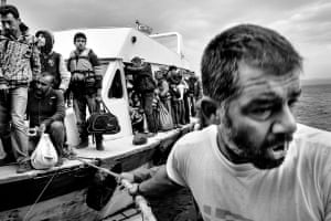A boat full of refugees, mostly Syrian and Afghanistani, prepare to land at Lesbos.