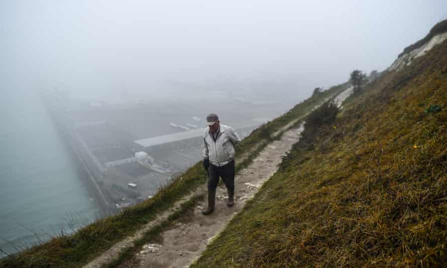 A man walks along the cliffs in Dover