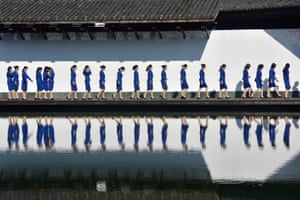 Zhejiang, China: Workers at the fifth World Internet Conference are reflected in water during a group photo session outside the venue in Wuzhen