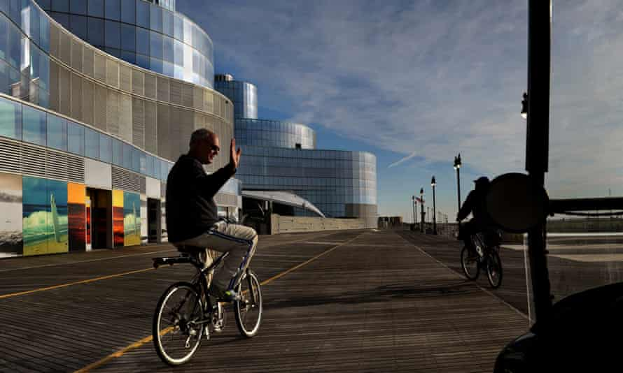 Atlantic City Mayor Don Guardian waves at a local walking the boardwalk as he passes the huge shuttered Revel casino.