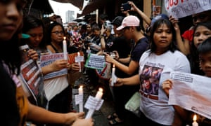 Protesters and residents hold lighted candles and placards at the wake of Kian Loyd delos Santos, a 17-year-old high school student, who was among the people shot dead last week in an escalation of President Rodrigo Duterte's war on drugs in Caloocan city, Metro Manila, Philippines