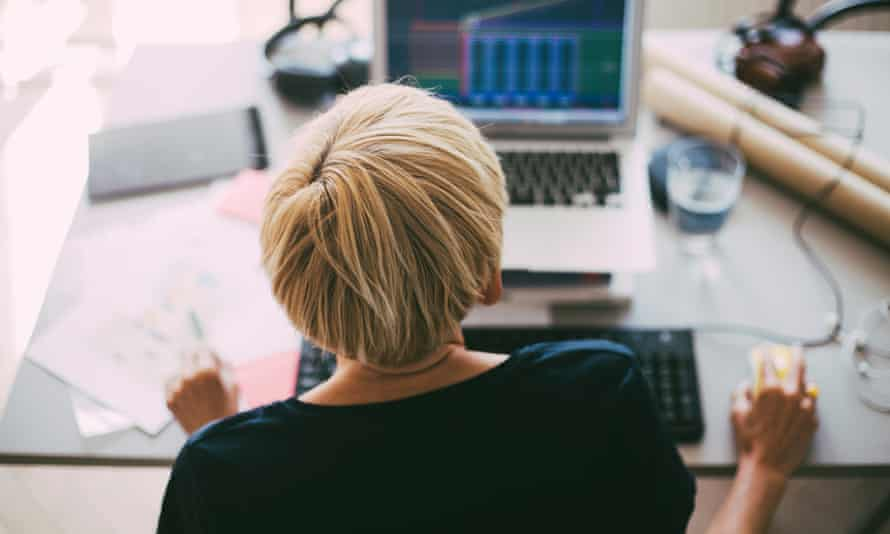 Rear view of woman working with laptop in office at home